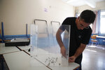 A municipal worker sets a ballot box at a voting center in Athens, on Friday, July 5, 2019. Greeks head to the polls in early general elections on Sunday, July 7. (AP Photo/Thanassis Stavrakis)
