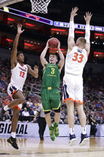 Oregon's Payton Pritchard (3) drives against Virginia's De'Andre Hunter (12) and Jack Salt (33) during the second half of a men's NCAA Tournament college basketball South Regional semifinal game, Thursday, March 28, 2019, in Louisville, Ky. (AP Photo/Michael Conroy)