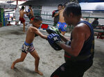 In this Wednesday, Nov. 14, 2018, photo, Thai kickboxer Chaichana Saengngern, 10-years old, spars at a training camp in Bangkok, Thailand. Thai lawmakers recently suggested barring children younger than 12 from competitive boxing, but boxing enthusiasts strongly oppose the change. They say the sport is part of Thai culture and gives poor families the opportunity to raise a champion that will lift their economic circumstances. (AP Photo/Sakchai Lalit)