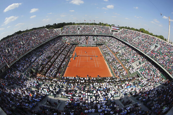 FILE - This May 27, 2015, file photo shows the center court at Roland Garros stadium, in Paris, France, as France's Gael Monfils plays his second round match against Argentina's Diego Schwarztman during the French Open tennis tournament. (AP Photo/David Vincent, File)