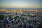 People sit at a panoramic vantage point overlooking the city of Barcelona, Spain, Monday, June 21, 2021. (AP Photo/Joan Mateu)