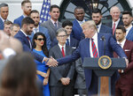 President Donald Trump, right, reaches over to shake hands with outfielder J.D. Martinez, left, while speaking during a ceremony on the South Lawn of the White House in Washington, Thursday, May 9, 2019, where he honored the 2018 World Series Baseball Champion Boston Red Sox. (AP Photo/Pablo Martinez Monsivais)