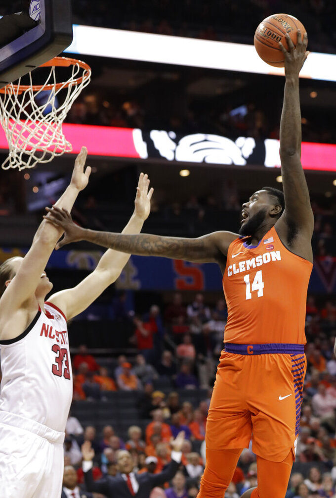 Clemson's Elijah Thomas (14) shoots over North Carolina State's Wyatt Walkern (33) during the first half of an NCAA college basketball game in the Atlantic Coast Conference tournament in Charlotte, N.C., Wednesday, March 13, 2019. (AP Photo/Chuck Burton)