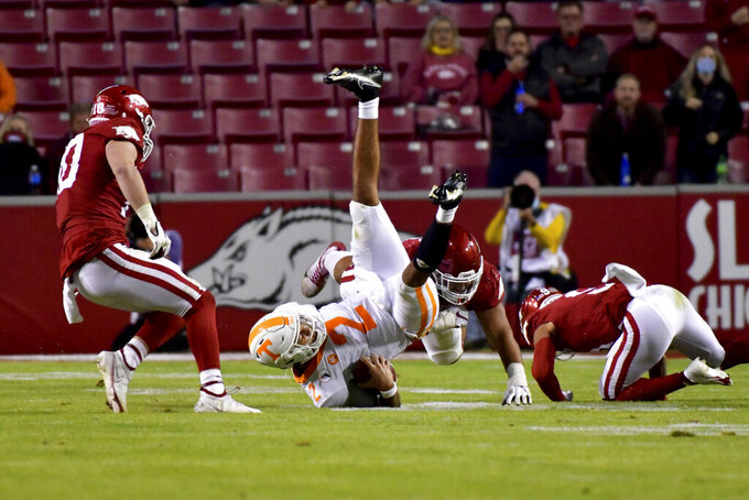 Tennessee quarterback Jarrett Guarantano (2) is tackled by Arkansas defenders during the second half of an NCAA college football game Saturday, Nov. 7, 2020, in Fayetteville, Ark. (AP Photo/Michael Woods)