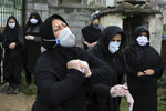 FILE - In this April 30, 2020, file photo, relatives of a victim who died from the coronavirus, mourn at the gate of a cemetery, in the outskirts of the city of Babol, in north of Iran. As coronavirus infections reached new heights in Iran, overwhelming its hospitals and driving up its death toll, the country's health minister gave a rare speech criticizing his own government's refusal to enforce basic health measures. (AP Photo/Ebrahim Noroozi, File)