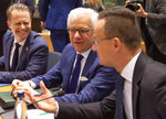 Polish Foreign Minister Jacek Czaputowicz, center, speaks with Hungarian Foreign Minister Peter Szijjarto, right, during a meeting of EU foreign ministers at the Europa building in Brussels, Monday, Dec. 9, 2019. European Union foreign ministers are debating how to respond to a controversial deal between Turkey and Libya that could give Ankara access to a contested economic zone across the Mediterranean Sea. (AP Photo/Virginia Mayo)