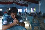 Nehemias Merino, a survivor of last year's landslide, participates in a day of prayers at the Siloe Church, in Los Angelitos, El Salvador, Sunday, Aug. 1, 2021. Merino and his mother survived the landslide that killed his brother Adolfo. (AP Photo/Salvador Melendez)