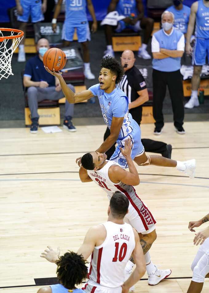 North Carolina guard Puff Johnson (14) leaps over UNLV guard Marvin Coleman (31) to shoot for the basket in the second half of an NCAA college basketball game in the Maui Invitational tournament, Monday, Nov. 30, 2020, in Asheville, N.C. (AP Photo/Kathy Kmonicek)