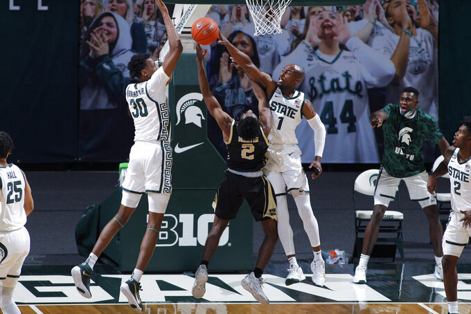 Michigan State's Joshua Langford (1) and Marcus Bingham Jr. (30) both block a shot by Western Michigan's Adrian Martin (2) during the first half of an NCAA college basketball game, Sunday, Dec. 6, 2020, in East Lansing, Mich. (AP Photo/Al Goldis)