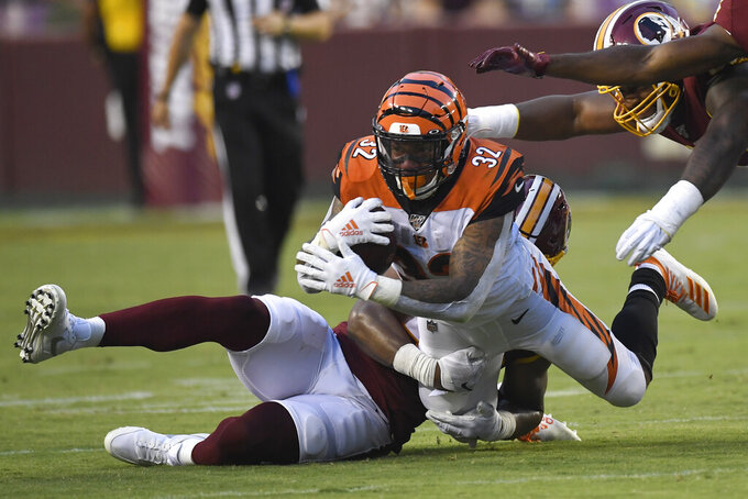 Cincinnati Bengals running back Trayveon Williams (32) is brought down by Washington Redskins linebacker Jon Bostic, back, during the first quarter of an NFL preseason football game in Landover, Md., Thursday, Aug. 15, 2019. (AP Photo/Susan Walsh)