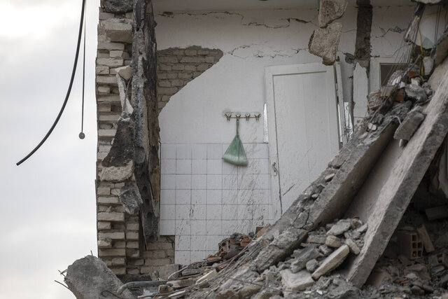 In this Wednesday, Nov. 27, 2019, a plastic bag with washing powder hangs on a wall of a collapsed building in Thumane, western Albania following a deadly earthquake.(AP Photo/Petros Giannakouris)