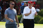 FILE - In this Friday, Dec. 29, 2017 file photo, President Donald Trump walks with Gene Gibson, commanding officer at Coast Guard Station Lake Worth Inlet, as he arrives to meet with members of the U.S. Coast Guard, who he invited to play golf, at Trump International Golf Club, in West Palm Beach, Fla. Trump will be the patient, not the commander in chief offering comfort, when he visits the Walter Reed military hospital. Trump heads to the medical facility in the Maryland suburbs of Washington on Friday, Jan. 12, 2018, for his first medical check-up as president. (AP Photo/Evan Vucci, File)