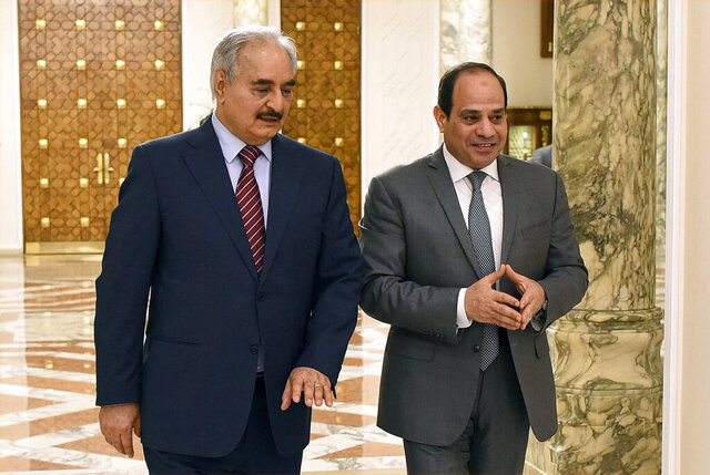 FILE - In this May 9, 2019 file photo, provided by Egypt's presidency media office, Egyptian President Abdel-Fattah el-Sissi, right, walks with military commander Khalifa Hifter, the head of the self-styled Libyan National Army, in Cairo, Egypt. Diplomats and intelligence officials from Egypt arrived in Libya's capital, Tripoli on Sunday, Dec. 27, 2020, the most senior Egyptian delegation to visit the western part of the north African country in years. Egypt views the instability in neighboring Libya as a national security threat and has backed Hifter who controls eastern and southern Libya, and attempted to seize Tripoli in a campaign collapsed earlier this year after Turkey's heavy military support to his rivals in Tripoli. (Egyptian Presidency Media office via AP, File)