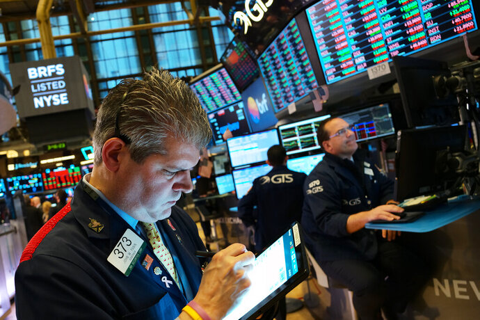 FILE - In this May 13, 2019, file photo John Panin monitors stock prices at the New York Stock Exchange. Corporate profits weren't as bad as analysts forecast in the first three months of the year, and S&P 500 companies may end up reporting no change in earnings when the expectations was for a drop. Wall Street is also getting less pessimistic about growth prospects for future quarters. That's key for stock prices, which tend to follow the path of corporate profits over the long term. But the U.S.-China trade war could dash the growing optimism. (AP Photo/Mark Lennihan, File)