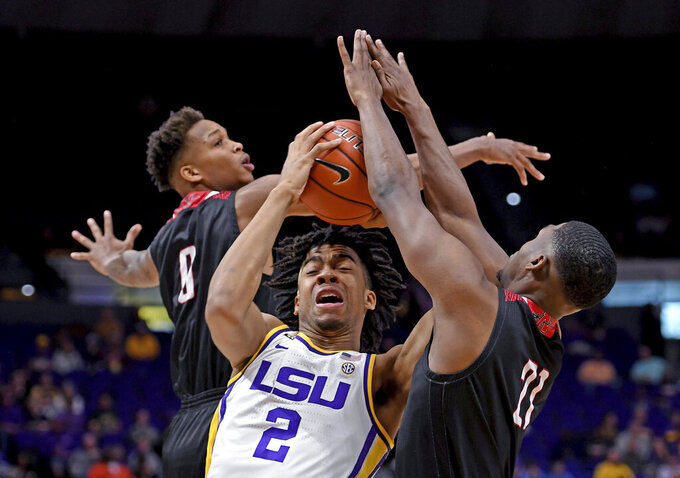 LSU forward Trendon Watford (2) drives the to the basket through heavy traffic from Nicholls defenders guards D'Angelo Hunter (0), left, and Brandon Moore Jr. (21), right, in the first half of an NCAA college basketball game, Saturday, Nov. 16, 2019, in Baton Rouge, La. (AP Photo/Bill Feig)