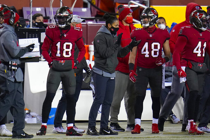 Tampa Bay Buccaneers assistant strength/conditioning coach Maral Javadifar, center, is seen with players during the second half of an NFL wild-card playoff football game against the Washington Football Team, Saturday, Jan. 9, 2021, in Landover, Md. (AP Photo/Julio Cortez)