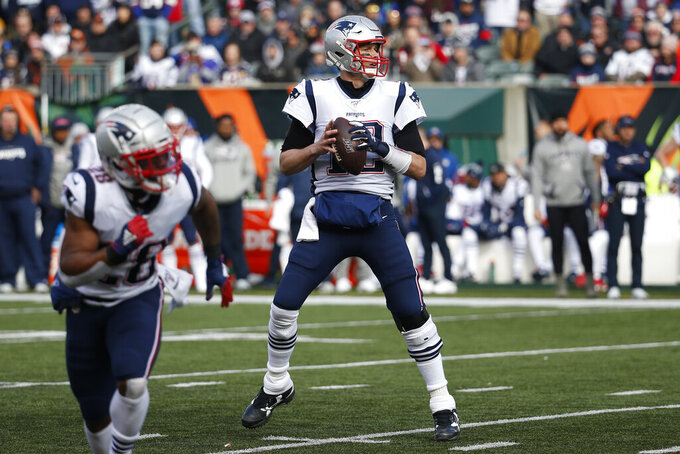 New England Patriots quarterback Tom Brady (12) looks to pass before throwing for a touchdown in the first half of an NFL football game against the Cincinnati Bengals, Sunday, Dec. 15, 2019, in Cincinnati. With this touchdown pass Brady surpasses Peyton Manning for the most seasons with 20+ touchdown passes in NFL history. (AP Photo/Frank Victores)