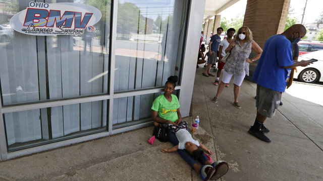 People wait in line at the Ohio Bureau of Motor Vehicles office, Tuesday, May 26, 2020, in University Heights, Ohio. Tuesday was the first day open for the Ohio BMV since they closed due to the coronavirus. (AP Photo/Tony Dejak)