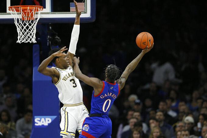 Kansas's Marcus Garrett (0) goes up for a shot against Villanova's Brandon Slater (3) during the first half of an NCAA college basketball game, Saturday, Dec. 21, 2019, in Philadelphia. (AP Photo/Matt Slocum)