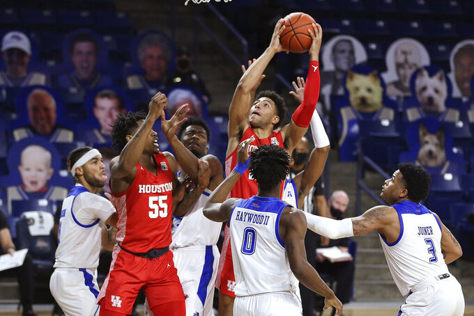 Houston's Quentin Grimes drives to the basket in heavy traffic during the second half of the team's NCAA college basketball game against Tulsa in Tulsa, Okla., Tuesday, Dec. 29, 2020. Tulsa won 65-64. (AP Photo/Dave Crenshaw)