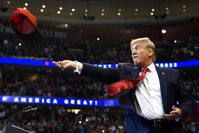 President Donald Trump throws a hat as he arrives to speak at a campaign rally in Sunrise, Fla., Tuesday, Nov. 26, 2019. Trump will join the rest of his family and spend the Thanksgiving holiday at his Mar-a-Lago estate. (AP Photo/Susan Walsh)