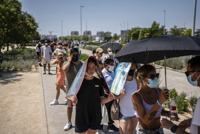 People protect themselves from the sun while waiting to be vaccinated against COVID-19 at the Isabel Zendal Hospital in Madrid, Spain, Tuesday, July 20, 2021. Spain is trying to stamp out a new wave of COVID-19 among its youth thanks to a robust vaccination program that is widely supported. Spain like the rest of the European Union got off to a slow start to compared to the United States and Britain when the first vaccines were released. But it has quickly made up ground once deliveries by drug makers started flowing. (AP Photo/Olmo Calvo)