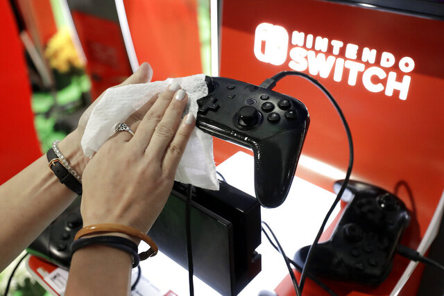 Game demonstrator Alex Chang, of New York, N.Y., hands only, uses a disinfectant wipe to clean a game console at the Nintendo Switch exhibit, Thursday, Feb. 27, 2020 at the Pax East conference, in Boston. A Nintendo Switch employee said that the coronavirus played a role in taking extra measures to keep gaming equipment clean at the conference. (AP Photo/Steven Senne)