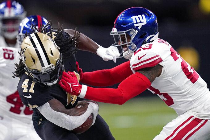 New York Giants cornerback Logan Ryan (23) tackles New Orleans Saints running back Alvin Kamara (41) in the first half of an NFL football game in New Orleans, Sunday, Oct. 3, 2021. (AP Photo/Brett Duke)