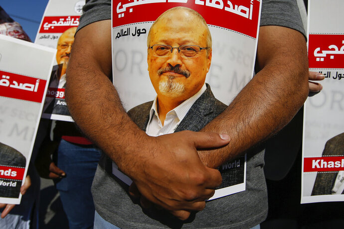 People hold posters of slain Saudi journalist Jamal Khashoggi, near the Saudi Arabia consulate in Istanbul, marking the two-year anniversary of his death, Friday, Oct. 2, 2020. The gathering was held outside the consulate building, starting at 1:14 p.m. (1014 GMT) marking the time Khashoggi walked into the building where he met his demise. The posters read in Arabic:' Khashoggi's Friends Around the World'. (AP Photo/Emrah Gurel)