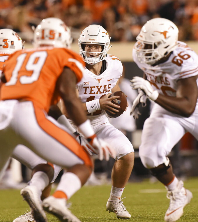 Texas quarterback Sam Ehlinger, center, looks at Oklahoma State linebacker Justin Phillips, left, while offensive lineman Calvin Anderson races by in the first half of an NCAA college football game in Stillwater, Okla., Saturday, Oct. 27, 2018. Oklahoma State defeated Texas 35-38.(AP Photo/Brody Schmidt)