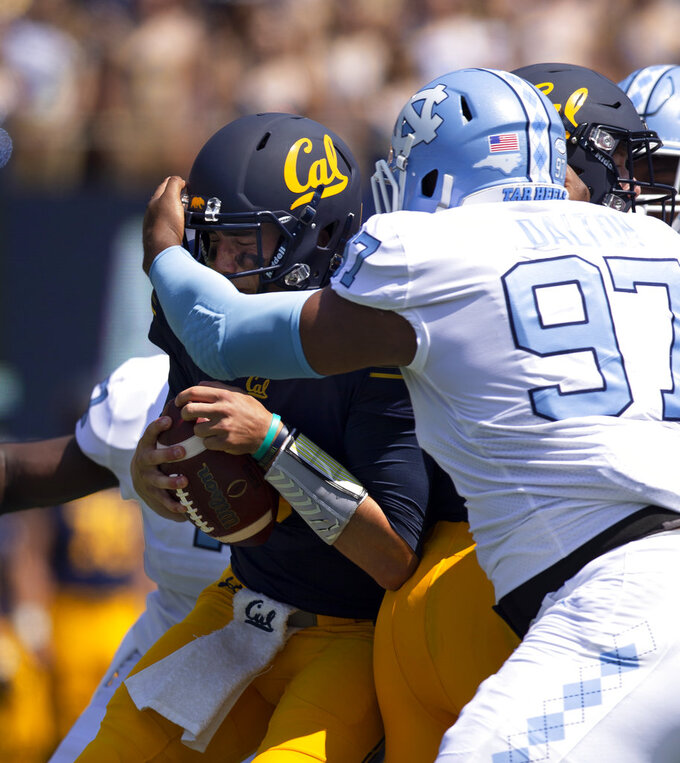 California quarterback Ross Bowers, left, is sacked for a loss by North Carolina defensive lineman Jalen Dalton (97) during the first half of an NCAA college football game, Saturday, Sept. 1, 2018, in Berkeley, Calif. (AP Photo/D. Ross Cameron)