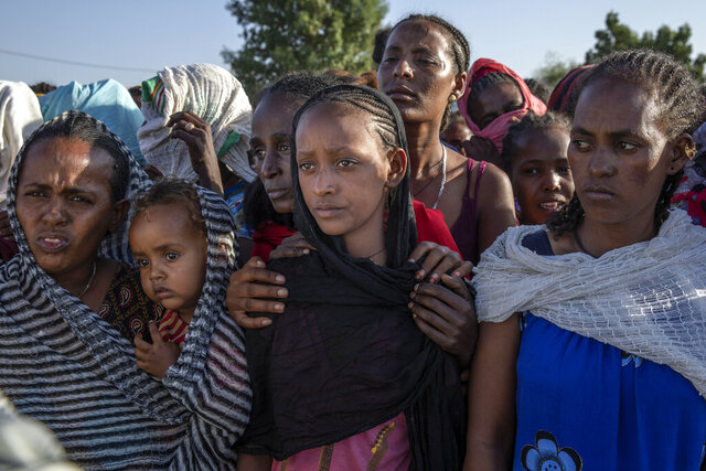 Tigray women who fled a conflict in the Ethiopia's Tigray region, wait to receive aid at Village 8, the transit centre near the Lugdi border crossing, eastern Sudan, Sunday, Nov. 22, 2020. Ethiopia's military is warning civilians in the besieged Tigray regional capital that there will be
