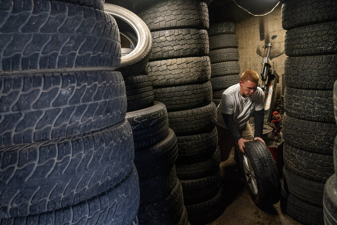 "Steven Ash, 33, works at the tire shop his family owns in Huntington, W.Va., Wednesday, March 17, 2021, and where he overdosed just days before. Ash was 19 when he took his first OxyContin pill and his life spiraled after that. The last year has been particularly brutal. He took more drugs to numb the pain, but it made things worse, a vicious cycle, he said, but he isn't sure how to escape it. He knows he's putting his mother through hell. ""I fight with myself every day. It's like I've got two devils on one shoulder and an angel on the other,"" he said. ""Who is going to win today?"" (AP Photo/David Goldman)"