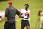 Atlanta Falcons wide receiver Calvin Ridley, right, laughs with head coach Arthur Smith, left, during NFL football practice Friday, July 30, 2021, in Flowery Branch, Ga. (AP Photo/Brynn Anderson)