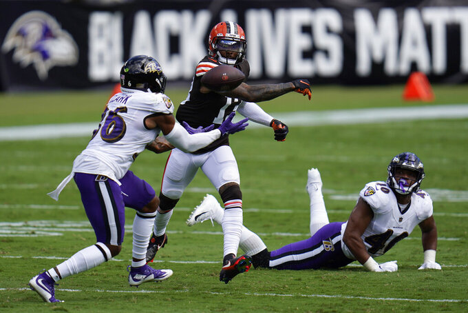 Baltimore Ravens safety Chuck Clark (36) attempts to intercept the ball as Cleveland Browns wide receiver Odell Beckham Jr. (13) tries to hit it away, during the first half of an NFL football game, Sunday, Sept. 13, 2020, in Baltimore, MD. Baltimore Ravens linebacker Malik Harrison (40) in on the ground. (AP Photo/Julio Cortez)