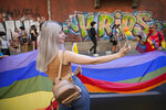 A young woman shoots a selfie picture during the Bucharest Pride 2021 in Bucharest, Romania, Saturday, Aug. 14, 2021. The 20th anniversary of the abolishment of Article 200, which authorized prison sentences of up to five years for same-sex relations, was one cause for celebration during the gay pride parade and festival held in Romania's capital this month. People danced, waved rainbow flags and watched performances at Bucharest Pride 2021, an event that would have been unimaginable a generation earlier. (AP Photo/Vadim Ghirda)