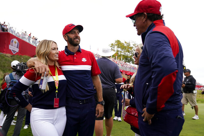 Team USA assistant captain Phil Mickelson talks to Team USA's Dustin Johnson and Paulina Gretzky after a Ryder Cup singles match at the Whistling Straits Golf Course Sunday, Sept. 26, 2021, in Sheboygan, Wis. (AP Photo/Ashley Landis)