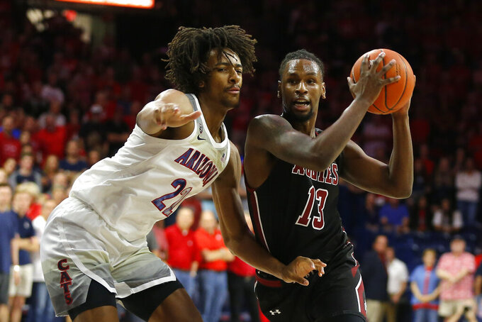 New Mexico State forward C.J. Bobbitt (13) drives on Arizona forward Zeke Nnaji in the first half of an NCAA college basketball game, Sunday, Nov. 17, 2019, in Tucson, Ariz. (AP Photo/Rick Scuteri)