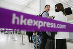 FILE - In this March 26, 2019 file photo, passengers wait at the check-in counter of Hong Kong Express Airways at the Hong Kong International Airport. The airline Hong Kong Express has apologized Friday, Jan. 17, 2020 for having required some female passengers bound for the U.S. territory of Saipan to take pregnancy tests.  (AP Photo/Kin Cheung, File)