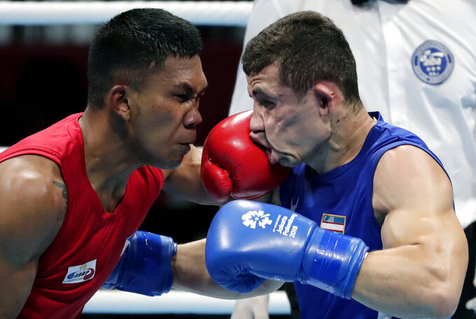 FILE - In this Aug. 31, 2018, file photo, Phillippines' Eumir Felix Marcial, left, and Uzbekistan's Israil Madrimov fight in their men's middleweight boxing semifinal at the 18th Asian Games in Jakarta, Indonesia. Professional boxers will fight at the Olympics this month for the second time following a century of exclusively amateur competition in the sport. More than 40 fighters with pro experience are listed in the Tokyo Olympic field, a sharp increase from just three pros in Rio de Janeiro. (AP Photo/Lee Jin-man, File)