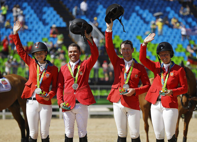 FILE - In this Aug. 17, 2016, file photo, from left, United States' Lucy Davis, Kent Farrington, McLain Ward and Elizabeth Madden celebrate after winning a silver medal in the equestrian team jumping competition at the 2016 Summer Olympics in Rio de Janeiro, Brazil. Ward returns to the U.S. equestrian show jumping team for the Tokyo Olympics, where they'll be a new wrinkle – three-person teams instead of four. It's part of an IOC directive to cut down on competitor numbers in some sports. It means that in the team show jumping event, they'll no longer be a fourth, or worst, score to throw out, making it easier for the public and television audiences to understand the scoring system as the event proceeds. (AP Photo/John Locher,File)