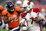 Arizona Cardinals quarterback Brett Hundley (7) tries to elude the reach of Denver Broncos linebacker Justin Hollins (52) during the first half of an NFL preseason football game, Thursday, Aug. 29, 2019, in Denver. (AP Photo/Jack Dempsey)