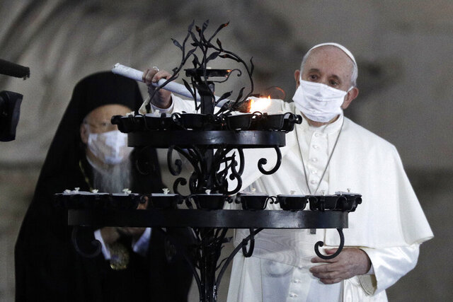 Pope Francis lights a candle for peace during an inter-religious ceremony for peace in the square outside Rome's City Hall, Tuesday, Oct. 20, 2020 (AP Photo/Gregorio Borgia)
