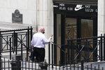 A man enters the New York Stock Exchange, Monday, Aug. 31, 2020, in New York. (AP Photo/Mark Lennihan)