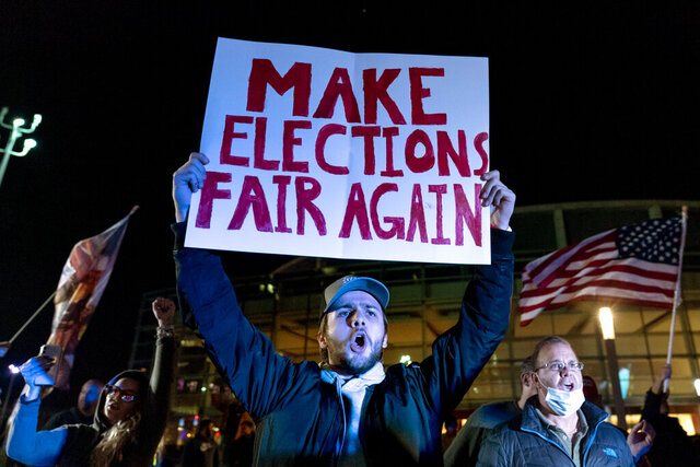 "FILE - In this Nov. 5, 2020, file photo, Jake Contos, a supporter of President Donald Trump, chants during a protest against the election results outside the central counting board at the TCF Center in Detroit. President Donald Trump and his allies have fomented the idea of a ""rigged election"" for months, promoting falsehoods through various media and even lawsuits about fraudulent votes and dead voters casting ballots. While the details of these spurious allegations may fade over time, the scar it leaves on American democracy could take years to heal. (AP Photo/David Goldman, File)"