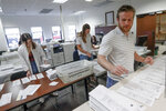 Processing work on mail in ballots for the Pennsylvania Primary election is being done by Emily Pellegrino, left, Danielle Beardsley, center, and Tim Vernick at the Butler County Bureau of Elections, Thursday, May 28, 2020, in Butler, Pa. Some county and state officials are warning that a flood of mailed-in ballots in Pennsylvania, fueled by fears of in-person voting during the coronavirus pandemic, will create a number of problems in Tuesday's primary election that must be fixed before they cause a disaster in this battleground state in November's presidential election. (AP Photo/Keith Srakocic)