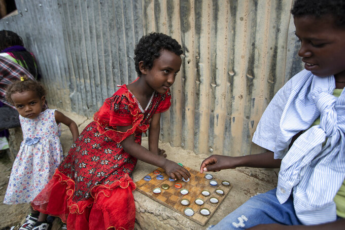 Elena, 7, left, plays a game of checkers using soda bottle tops with friend Hailemariam, 12, at a reception and day center for displaced Tigrayans in Mekele, in the Tigray region of northern Ethiopia, Sunday, May 9, 2021. The Tigray conflict has displaced more than 1 million people, the International Organization for Migration reported in April, and the numbers continue to rise. Some thousands of Eritrean refugees are among the most vulnerable groups in the Tigray conflict and are increasingly caught in the middle of the conflict in Ethiopia's Tigray region. (AP Photo/Ben Curtis)