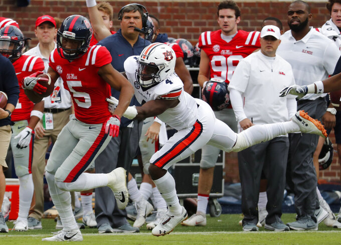 Mississippi wide receiver DaMarkus Lodge (5) pulls away with a first down pass reception from Auburn defensive back Noah Igbinoghene during the first half of an NCAA college football game against on Saturday, Oct. 20, 2018, in Oxford, Miss. Auburn won 31-16. (AP Photo/Rogelio V. Solis)