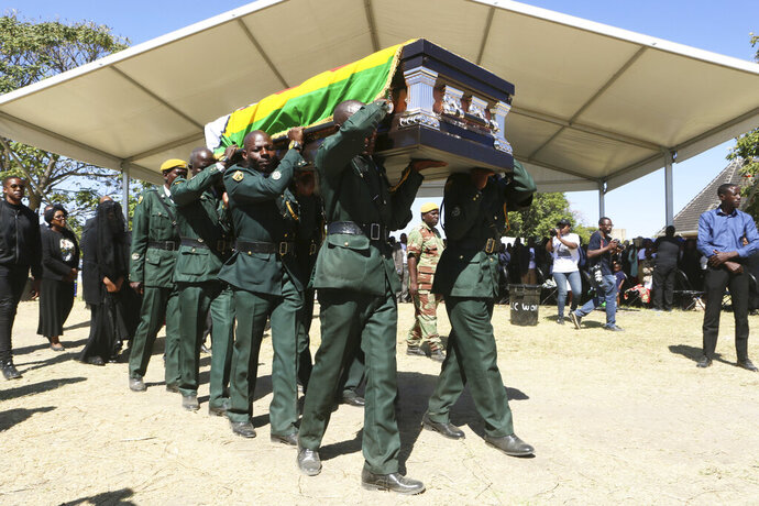 The coffin carrying the body of former Zimbabwean President Robert Mugabe is seen at during mass at his rural home in Zvimba, about 100 kilometers north west of the capital Harare, Saturday. Sept, 28, 2019. According to a family spokesperson Mugabe is expected to be buried at the residence after weeks of drama mystery and contention over his burial place. (AP Photo/Tsvangirayi Mukwazhi)