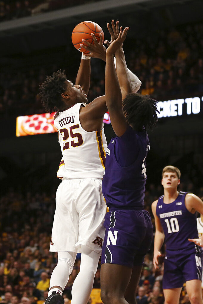 Minnesota's Daniel Oturu shoots the ball over Northwestern's Jared Jones during an NCAA college basketball game Sunday, Jan. 5, 2020, in Minneapolis. (AP Photo/Stacy Bengs)